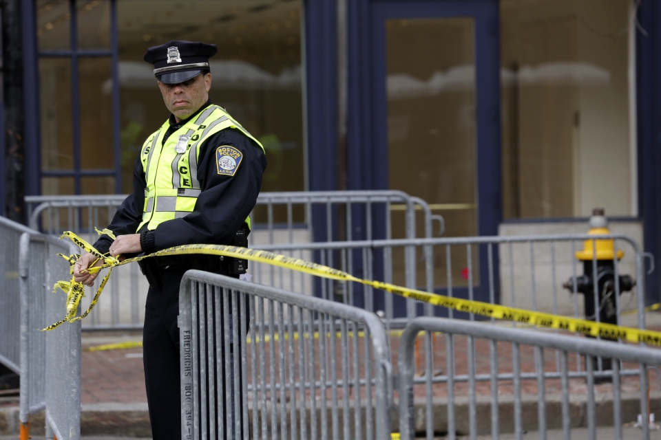 A Boston Police officer ties caution tape in the downtown area near Copley Square one day after a pair of bombs exploded at the finish line of the Boston Marathon, in Boston, Tuesday, April 16, 2013. (AP / Julio Cortez)