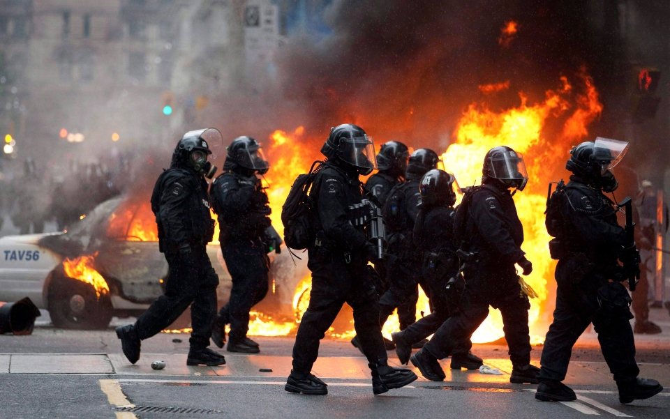 Riot police walk by a burning police car in downtown Toronto during anti G20 protests on Saturday, June 26, 2010. (The Canadian Press/Frank Gunn)