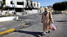 A man carrying a bag of food walks past a burned-out police station in Tripoli, Libya, Saturday, Feb. 26, 2011. (AP / Ben Curtis)
