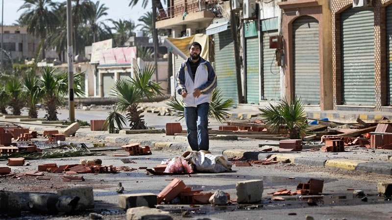 A man walks through roadblocks made by residents in the Tajoura district of eastern Tripoli, Libya, Saturday, Feb. 26, 2011.  (AP / Ben Curtis)