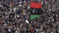 Libyan protesters shouts slogan against Libyan leader Moammar Ghadafi during a demonstration in the court square, in Benghazi, Libya, on Friday Feb. 25, 2011. (AP Photo/Hussein Malla)