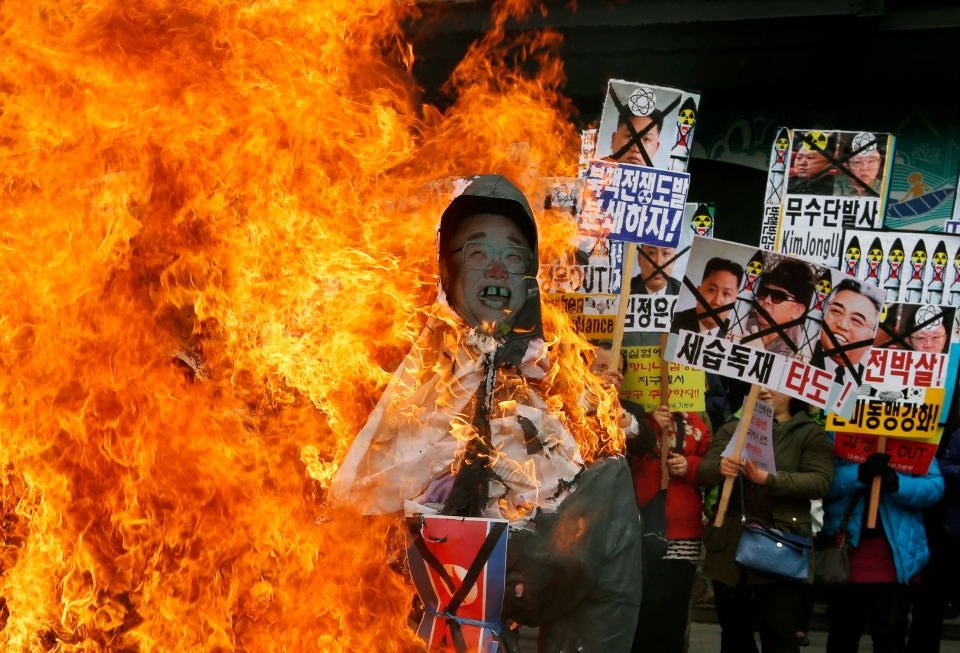 South Korean protesters burn effigies of North Korean leader Kim Jong-Un, and late leaders Kim Jong Il and Kim Il Sung at an anti-North Korea protest on the birthday of Kim Il Sung in Seoul, South Korea, April 15, 2013. (AP / Kin Cheung)