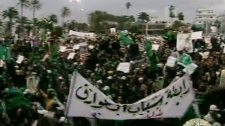 In this image taken from Libya State Television, showing a banner declaring that the Tuareg Libyan ethnic group is attending, a crowd listens to Libyan leader Moammar Gadhafi, not pictured, at The Green Square, central Tripoli, Libya, as broadcast Friday, Feb. 25, 2011. (AP Photo/Libya State)