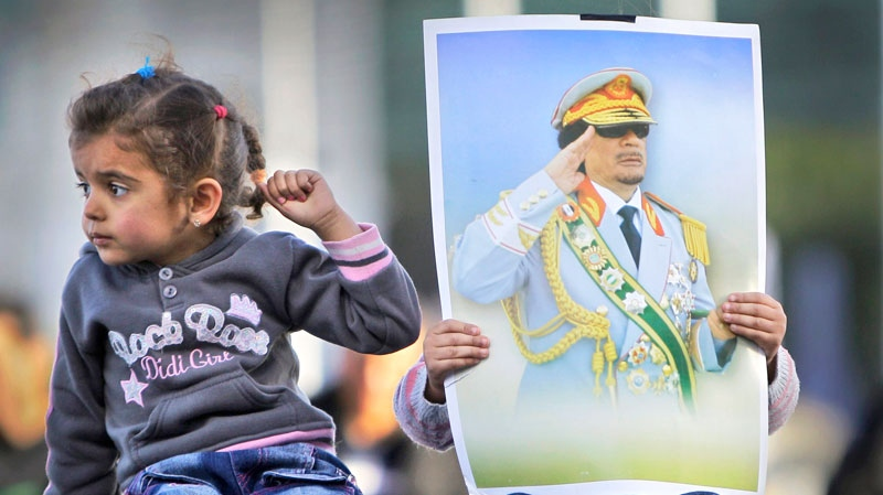 Two children of pro-Gadhafi supporters, one holding a poster of the Libyan leader, sit on the roof of a parked car next to a pro-regime rally of around 100 supporters in Green Square, Tripoli, Libya Saturday, Feb. 26, 2011. (AP / Ben Curtis)