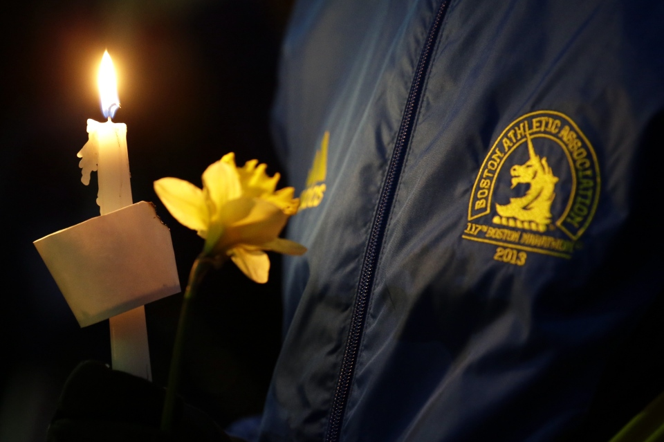 Lizzie Lee, 56, of Lynwood, Wash., who was participating in her first Boston Marathon, holds a candle and a flower at Boston Common during a vigil for the victims of the Boston Marathon explosions, Tuesday, April 16, 2013. (AP / Julio Cortez)