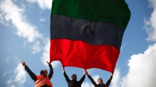 Libyans wave the former royal flag of Libya during a protest in the eastern city of Benghazi, Libya, Saturday, Feb. 26, 2011. (AP / Tara Todras-Whitehill)