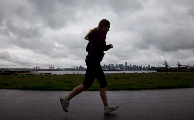 Rain clouds are seen over a silhouetted runner in North Vancouver, B.C., in this 2012 file photo. (Jonathan Hayward/THE CANADIAN PRESS)
