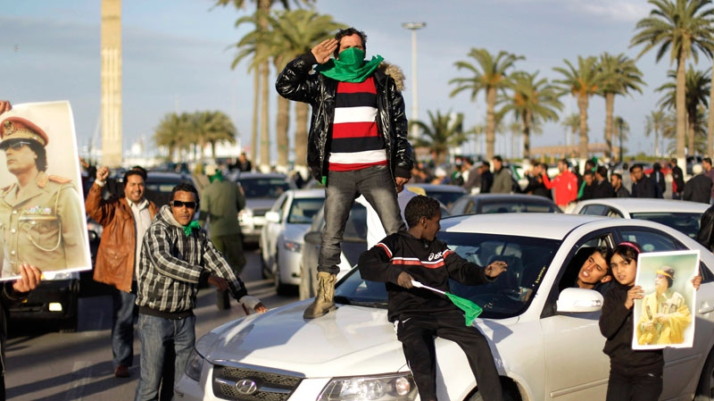 A pro-Gadhafi supporter salutes to others as he stands on the roof of a car arriving at a pro-regime rally of around 100 supporters in Green Square, Tripoli, Libya, Saturday, Feb. 26, 2011. (AP / Ben Curtis)