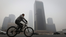A Chinese man rides his bicycle by buildings shrouded in thick haze in Beijing, Wednesday, Feb. 23, 2011. (AP Photo/Vincent Thian)