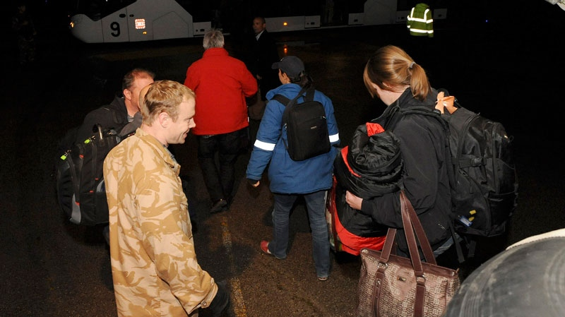 In this photo released by Britain's Ministry of Defence, civilians disembark from one of two Royal Air Force C130 Hercules that evacuated more than 150 civilians from desert locations south of Benghazi, at Malta's international airport, early Sunday, Feb. 27, 2011. (AP / Ministry of Defence, Cpl. Paul Randall, ho)