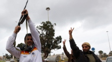 An anti-Libyan leader Moammar Gadhafi gunman, left, holds up his AK-47 shoots in the air in celebrating the freedom of the Libyan city of Benghazi, Libya, on Sunday Feb. 27, 2011. (AP / Hussein Malla)