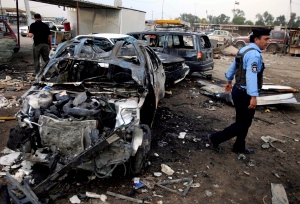 A policeman inspects the aftermath of a car bomb attack at a used cars dealers parking lot in Habibiya neighborhood of eastern Baghdad, Iraq, Tuesday, April 16, 2013. (AP / Karim Kadim)