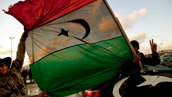 Libyan men hold the former royal flag as they drive past a demonstration against Libyan leader Moammar Gadhafi in Benghazi, in eastern Libya
