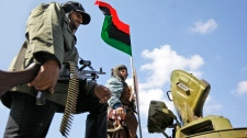 Armed residents stand on top of a captured tank flying a flag of Libya's monarchy prior to Moammar Gadhafi's reign, in the main square in Zawiya, 50 kilometres west of Tripoli, in Libya, Sunday, Feb. 27, 2011. (AP / Ben Curtis)