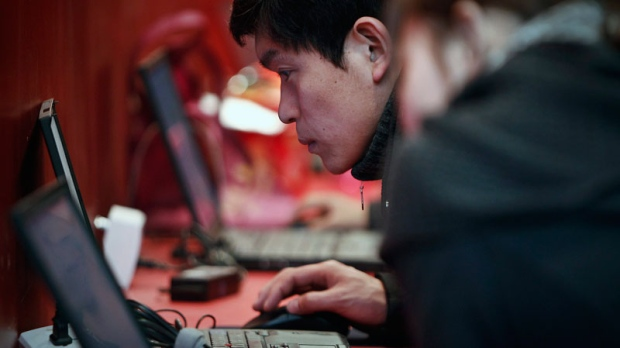 A Chinese man surfs free internet service at a booth at the China International Auto Accessories Commercial Expo in Beijing Saturday, Feb. 26, 2011. (AP / Andy Wong)