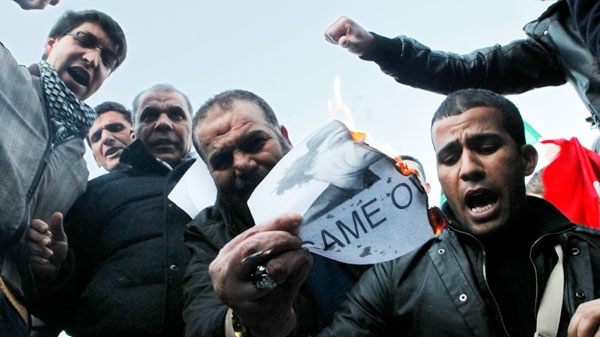"Men burn a banner with a picture of Moammar Gadhafi reading ""game over"" during a demonstration against Libyan leader Moammar Gadhafi in the centre of Madrid, Spain, Sunday, Feb. 27, 2011. (AP / Andres Kudacki)"
