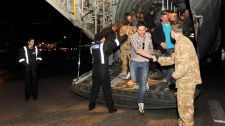 Civilians disembark from one of two Royal Air Force C130 Hercules that evacuated more than 150 civilians from desert locations south of Benghazi, at Malta's international airport, early Sunday, Feb. 27, 2011. (AP / Ministry of Defence, Cpl. Paul Randall)