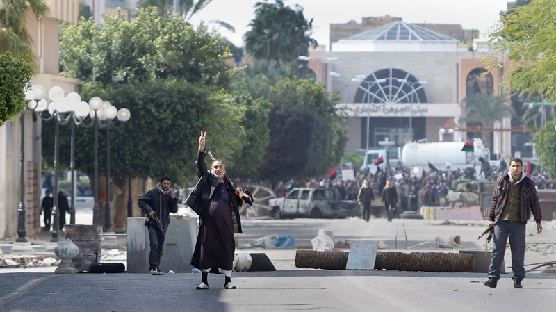 A gunman flashes the victory sign to beckon foreign journalists to come closer past barricades to see the situation in the main square in Zawiya, 30 miles (50 kilometers) west of Tripoli, in Libya Sunday, Feb. 27, 2011. (AP / Ben Curtis)