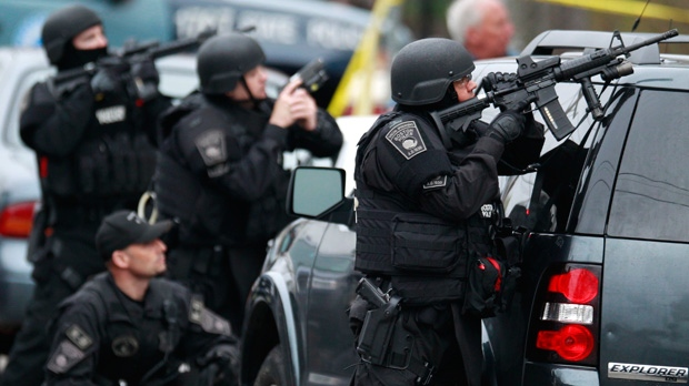 Police in tactical gear surround an apartment building while looking for a suspect in the Boston Marathon bombings in Watertown, Mass., Friday, April 19, 2013. (AP / Charles Krupa)