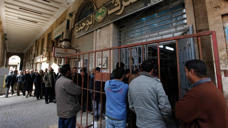 Libyan citizens queue outside a bank to get cash, in Benghazi, Libya, on Tuesday March 1, 2011. (AP / Hussein Malla)