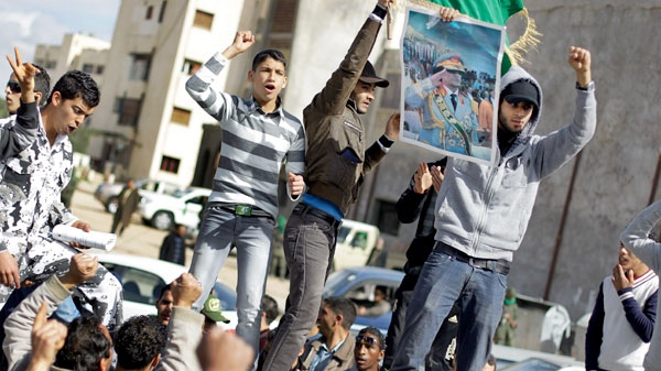Pro-Gadhafi supporters stage a small rally, during a government-provided tour for foreign media to see trucks carrying food aid which according to the government was headed to Benghazi, in Qasr Banashir, southeast of the capital Tripoli, in Libya, Tuesday, March 1, 2011. (AP / Ben Curtis)