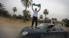A pro-Gadhafi supporter stands on a speeding car as he and other vehicles of supporters honk horns and drive on a road near Harshan, 10 kilometres east of Zawiya, in Libya, Monday, Feb. 28, 2011. (AP Photo/Ben Curtis)