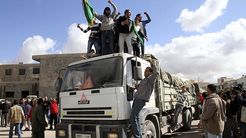 Supporters of Libya leader Moammar Gadhafi shout slogans on top of a truck of an aid convoy which consists of 18 trucks and an ambulance carrying food and medicines head to the eastern city of Benghazi, Libya, in the town of Qasr bin Ghashir, south of Tripoli, Tuesday, March 1, 2011. (AP / Xinhua, Hamza Turkia)