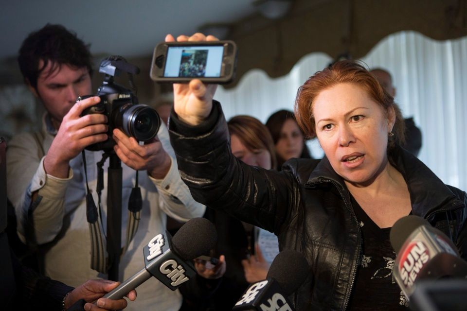 Maret Tsarnaeva, an aunt of the two suspects in the Boston Marathon bombing, holds a reporter's smart phone which displays a scene from the bomb site, as she speaks to journalists in the lobby of her apartment building in Toronto on Friday April 19, 2013. (Chris Young / THE CANADIAN PRESS)