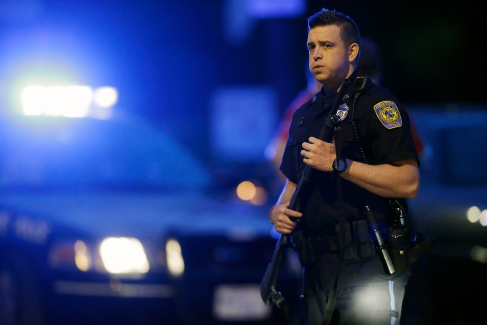 A police officer stands guard at the scene as the search for suspect in the Boston Marathon bombings continues , Friday, April 19, 2013, in Watertown, Mass. (AP / Matt Rourke)