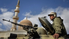 A pro-Gadhafi Libyan soldier sits in an armoured vehicle next to a mosque in Qasr Banashir, southeast of the capital Tripoli, in Libya, Tuesday, March 1, 2011. (AP / Ben Curtis)