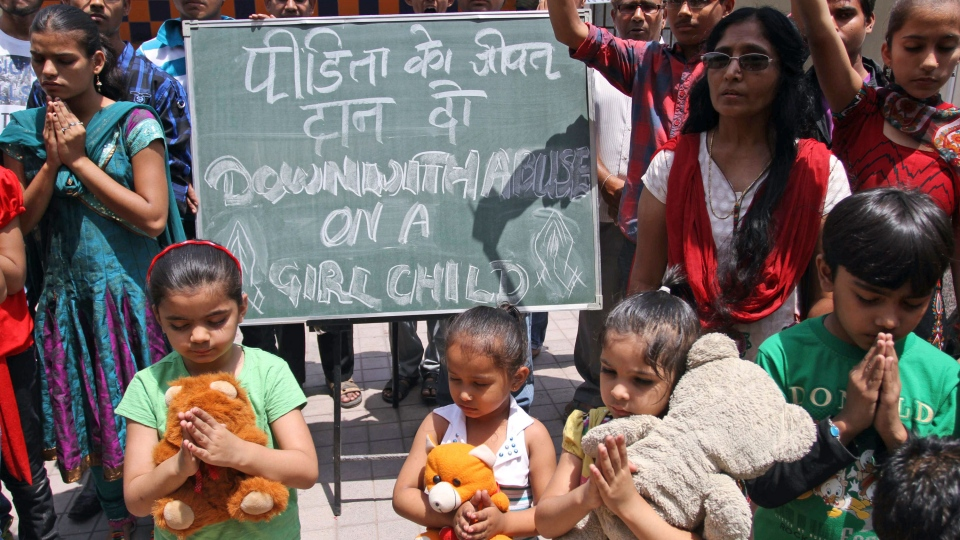 Young Indian girls join others as they pray for the speedy recovery of a 5-year-old girl who was raped and tortured in Delhi, in Ahmadabad, India, Saturday, April 20, 2013. (AP / Ajit Solanki)
