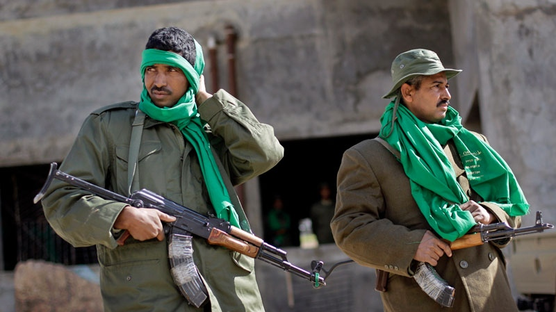 Unidentified Pro-Gadhafi security forces stand near a checkpoint on a street in Qasr Banashir, southeast of the capital Tripoli, in Libya, Tuesday, March 1, 2011.  (AP / Ben Curtis)