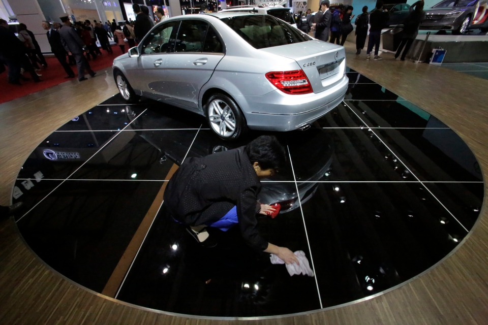 A cleaner wipes the floor where Mercedes Benz C260 is displayed at the Shanghai International Automobile Industry Exhibition (AUTO Shanghai) media day in Shanghai, China Saturday, April 20, 2013. (AP Photo/Eugene Hoshiko)