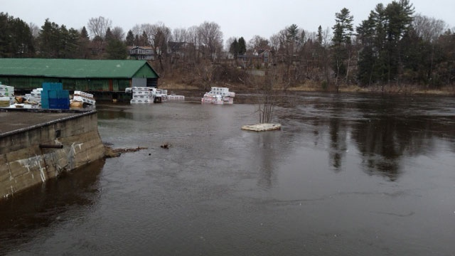 Water rushes through a lumber yard where a state of emergency was declared Friday due to flooding, in Bracebridge, Ont., Saturday, April 20, 2013. (John Musselman / CTV Toronto)