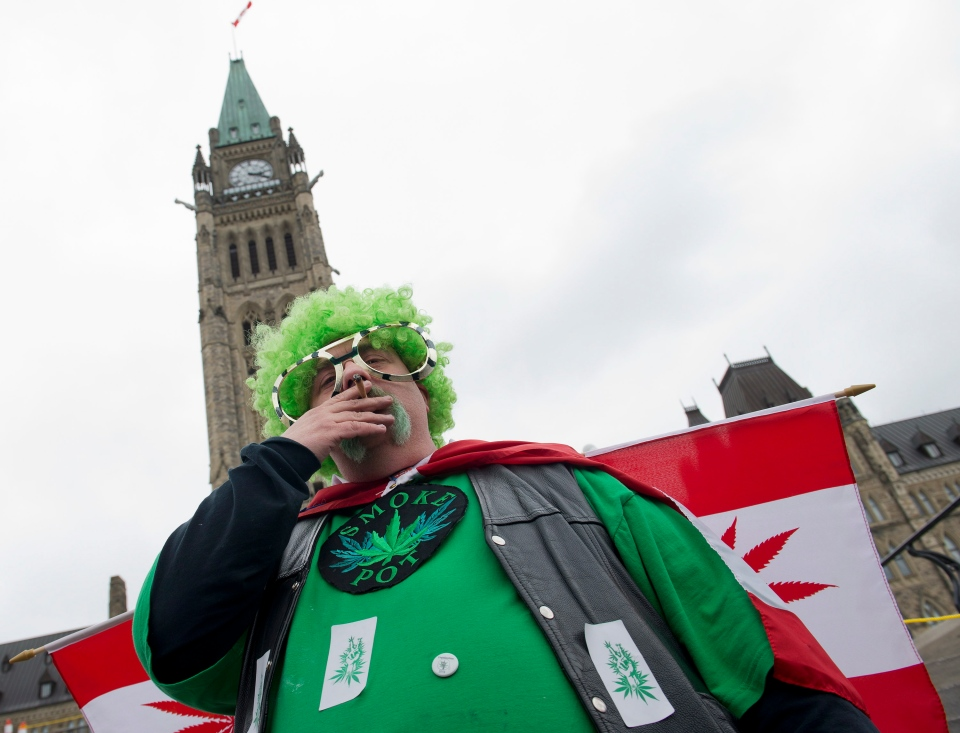 A man smokes a joint during the Fill the Hill marijuana rally on Parliament HIll in Ottawa on Saturday, April 20, 2013. (THE CANADIAN PRESS/Justin Tang)