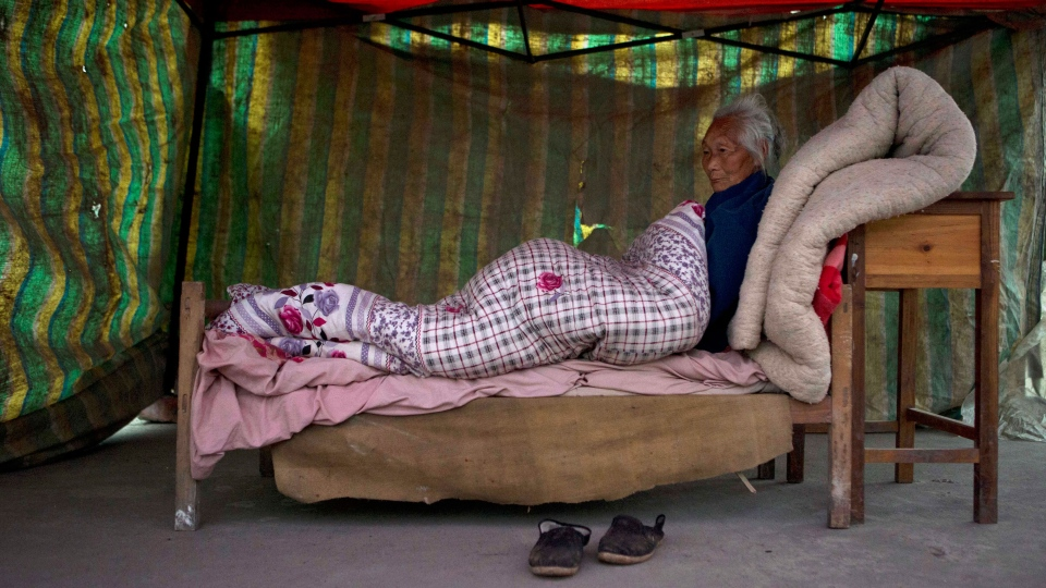 An elderly woman rests on a makeshift bed setup outdoors near Shangli town in southwestern China's Sichuan province, Sunday, April 21, 2013. (AP / Ng Han Guan)