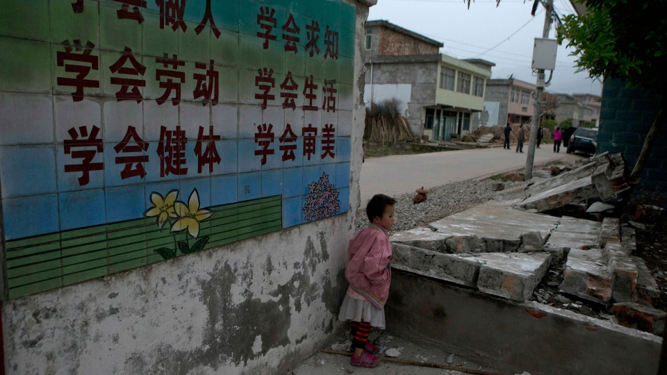 A child stands near a collapsed wall with slogans promoting education outside a school near Shangli town in southwestern China's Sichuan province, Sunday, April 21, 2013. (AP / Ng Han Guan)