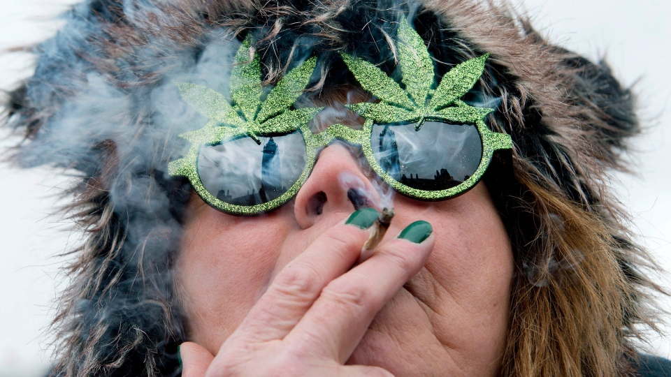 The Peace Tower is reflected in the sunglasses of a woman smoking a joint at the Fill the Hill marijuana rally on Parliament HIll in Ottawa on Saturday, April 20, 2013. (Justin Tang / THE CANADIAN PRESS)