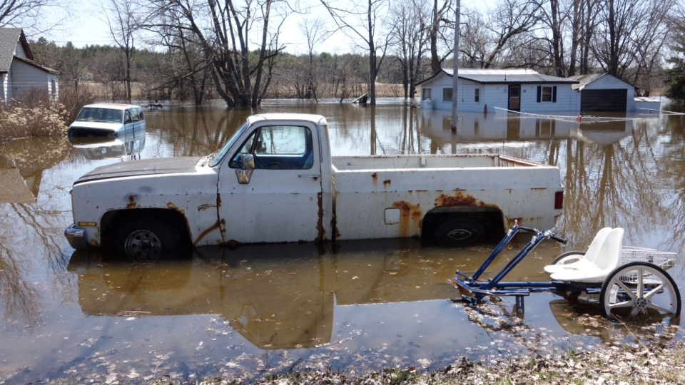 A truck is partially submerged in flood waters in a yard in Burnt River, Ont., Sunday, April 21, 2013. (Tom Podolec / CTV Toronto)