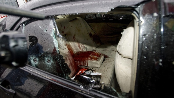 A Pakistani cameraman films the blood-stained damaged car of slain Pakistan's government minister for religious minorities Shahbaz Bhatti outside the emergency ward of a local hospital in Islamabad, Pakistan on Wednesday, March 2, 2011. (AP Photo/Anjum Naveed)