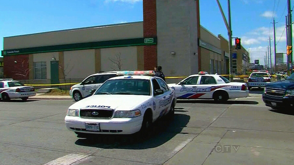Police vehicles block off a TD bank branch on St. Clair Avenue in Toronto, Sunday, April 21, 2013.
