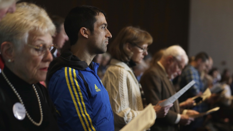 Wearing his Boston Marathon runner's jacket, David Delmar, 28, second from left, a member of Trinity Episcopal Church in Boston, attends a service at Temple Israel, which allowed the Trinity congregation to hold their service in Boston on Sunday, April 21, 2013. (AP / Julio Cortez)