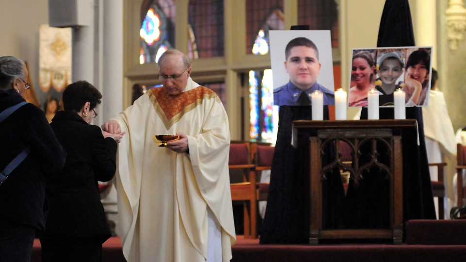 A parishioner receives communion during a Mass at the Cathedral of the Holy Cross in Boston honoring victims of the Boston Marathon bombings and MIT officer, Sean Collier on Sunday, April 21, 2013. (Boston Herald / Faith Ninivaggi)
