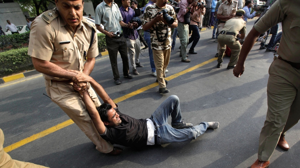 Indian policemen remove protestors shouting slogans outside the prime minister's residence during a protest against the rape of a 5-year-old girl in New Delhi, India, Sunday, April 21, 2013. (AP / Manish Swarup)