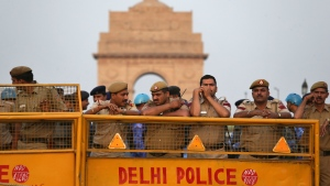 Indian policemen stand behind barricades to block protesters near the India Gate monument in New Delhi, India, Sunday, April 21, 2013. (AP / Manish Swarup)