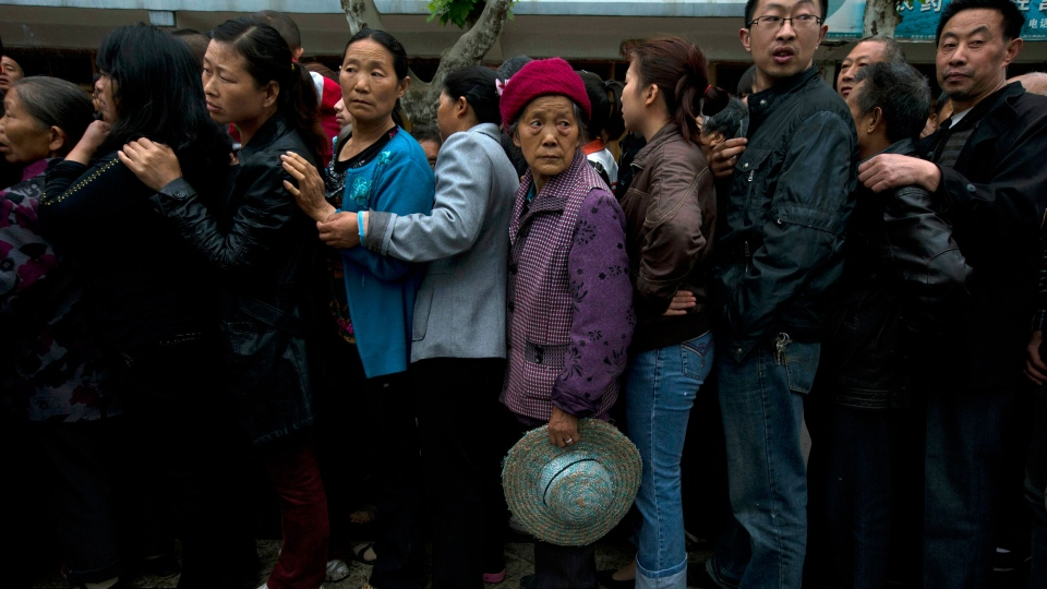 Residents line up for packets of instant noodles in the earthquake struck county of Lushan in southwestern China's Sichuan province, Monday, April 22, 2013. (AP / Ng Han Guan)