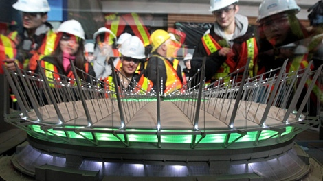 Students from King George Secondary School, on a B.C. government Year of Science tour, look at a model of what BC Place Stadium will look like when renovations are complete in Vancouver, B.C., on Wednesday March 2, 2011. (CP/Darryl Dyck)