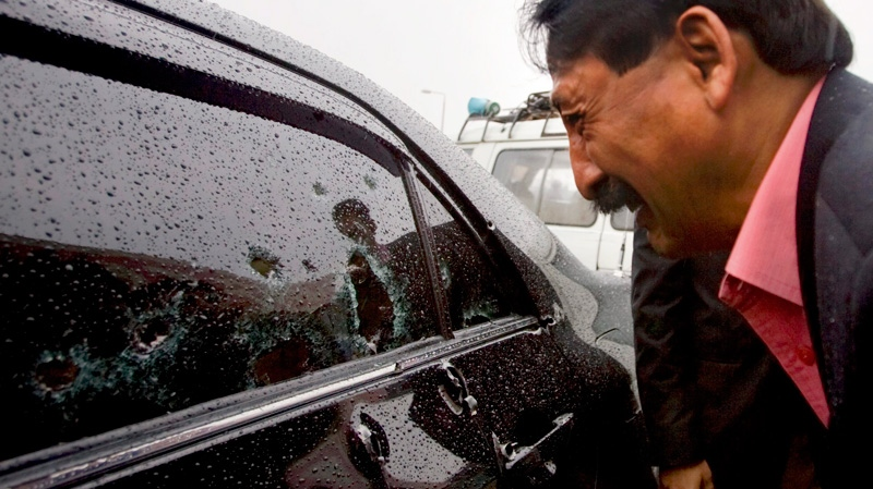 Wasif Ali Khan, a friend of Pakistan's government minister for religious minorities Shahbaz Bhatti looks at the bullet-riddled window of car while he mourns over the death of Bhatti outside a local hospital in Islamabad, Pakistan on Wednesday, March 2, 2011. (AP / Anjum Naveed)