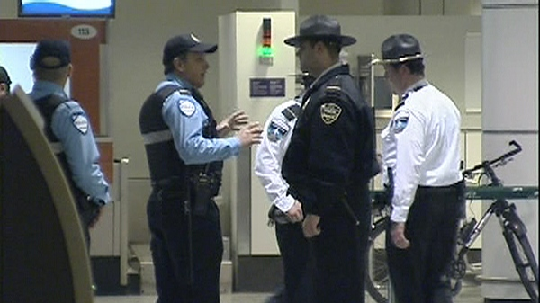 Police officers talk with security agents outside a security checkpoint at Trudeau International airport (March 3, 2011)