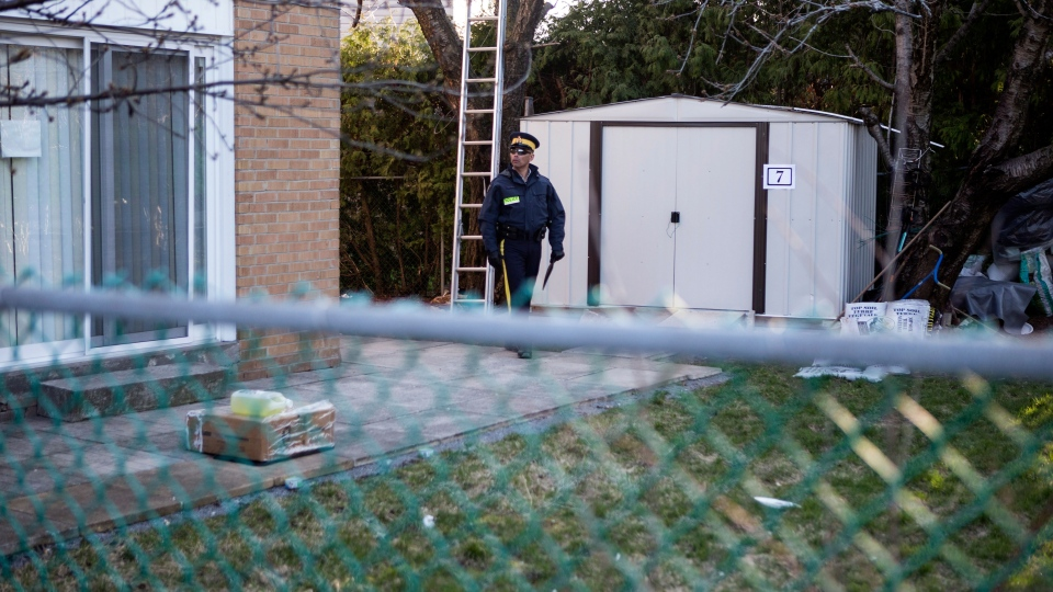 An RCMP officer stands outside the home of one of the two men accused of plotting a terror attack on a rail target, in Toronto on Monday, April 22, 2013. (Chris Young / THE CANADIAN PRESS)